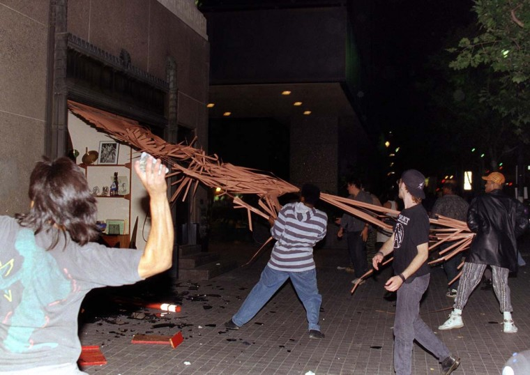 April 29, 1992: Rioters destroy an iron gate from a store in downtown Los Angeles hours after citywide rioting and looting broke out. (Wade Byars//AFP/Getty Images)