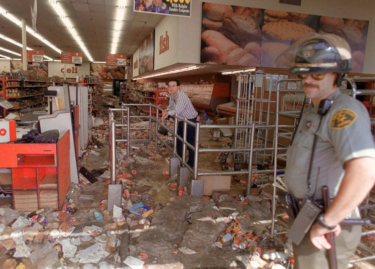 April 30, 1992: A store owner and a Los Angeles Police Department (LAPD) officer look at the damage caused by looters in Los Angeles. (Mike Nelson/AFP/Getty Images)