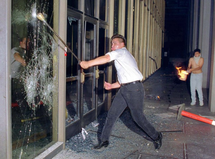 April 29, 1992: A rioter breaks a glass door of the Criminal Courts building, downtown Los Angeles after a jury acquitted four police officers accused of beating black motorist Rodney King in 1991. (Hal Garb/AFP/Getty Images)