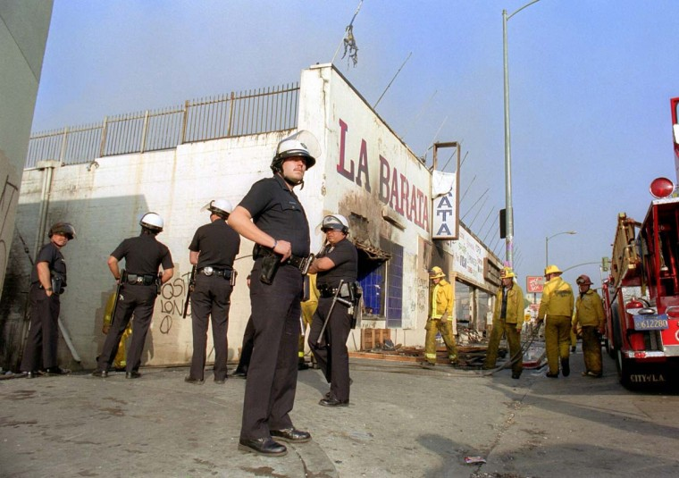 April 30, 1992: Los Angeles police officers in riot gear stand guard at a burned out grocery store near downtown Los Angeles. (Don Emmert/AFP/Getty Images)