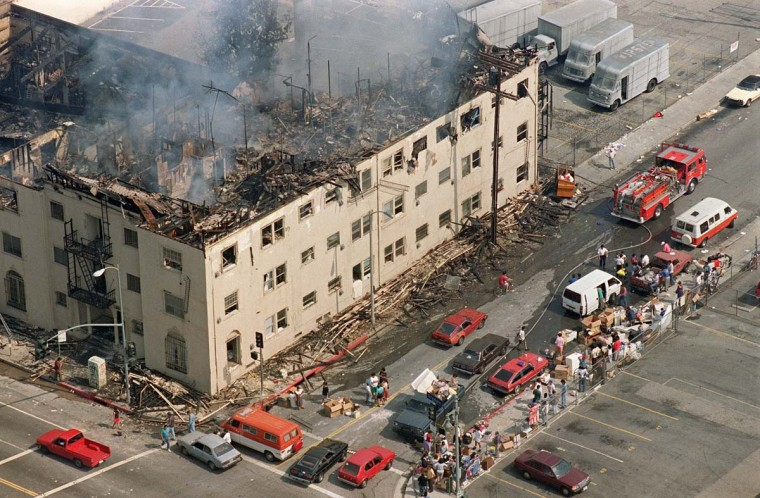 May 1, 1992: People with their belongings line a sidewalk across from a burned out apartment in Los Angeles. (Hal Garb/AFP/Getty Images)