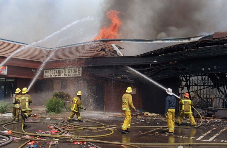 April 30, 1992: Firemen spraying a building going up in flames in South Los Angeles. (Hal Garb/AFP/Getty Images)