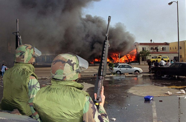 April 30, 1992: National Guardsmen watch a business go up in flames in South Los Angeles. (Hal Garb/AFP/Getty Images)