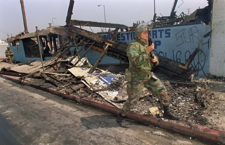 May 1, 1992: National Guardsmen patrol a destroyed area in central Los Angeles. (Hal Garb/AFP/Getty Images)
