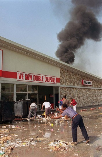 May 1, 1992: Merchants and volunteers cleaning up in front of a market that was burned and looted during riots in South Los Angeles. (Hal Garb/AFP/Getty Images)