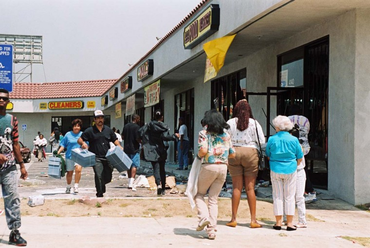 April 30, 1992: Looters carrying goods from a shopping center in Los Angeles. (Hal Garb/AFP/Getty Images)