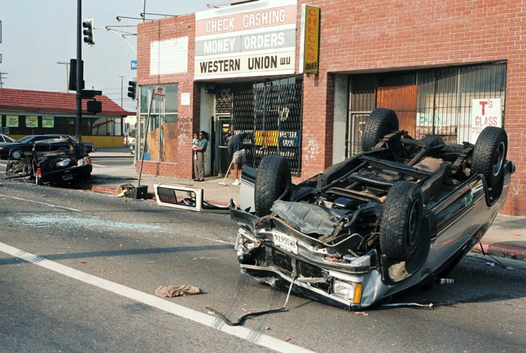 April 30, 1992: A car lies overturned in a street of Los Angeles as a merchant sweeps up in front of his shop. (Don Emmert/AFP/Getty Images)