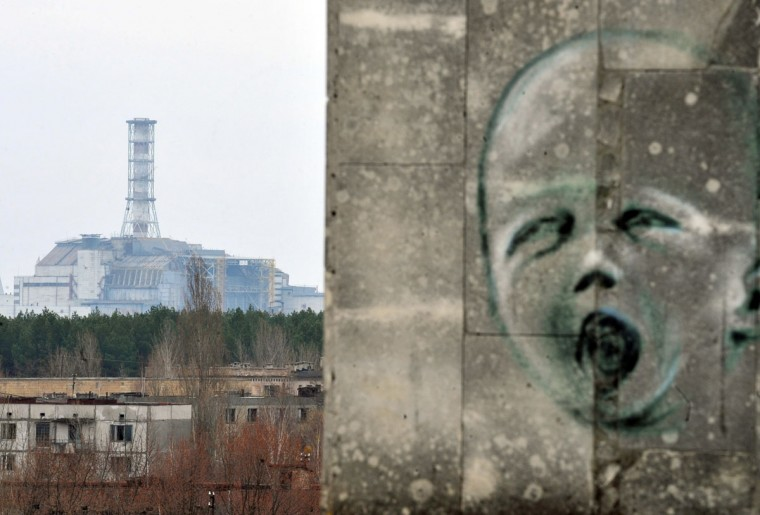April 4, 2011: Graffiti is pictured on a wall in the ghost city of Pripyat near the fourth nuclear reactor (background) at the former Chernobyl Nuclear power plant. A project to build a new sarcophagus over the damaged Chernobyl nuclear reactor lacks some 600 million euros of the 1.5 billion needed, a Ukrainian official said in March 2011. The concrete sarcophagus capping the reactor has developed cracks and is not considered failsafe.(Sergei Supinsky/AFP/Getty Images)
