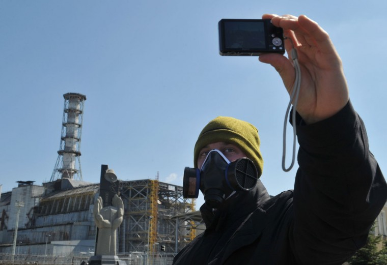 April 18, 2011: A visitor takes a self-portrait in front of the 4th power block of the Chernobyl Nuclear Power Plant. In the heart of Chernobyl, Ukrainian specialists regularly venture inside the concrete cover sheltering the ruined reactor after it exploded on April 26, 1986 to check its structure and radiation levels. (Sergei Supinsky/AFP/Getty Images)