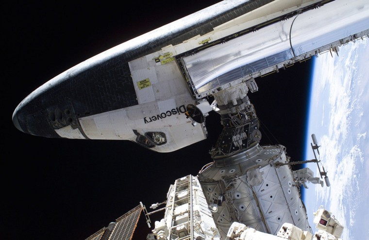 August 3, 2005: The Space Shuttle Discovery docked to the Destiny laboratory of International Space Station in this image photographed by astronaut Mission Specialist Stephen K. Robinson. Japanese Mission specialist Soichi Noguchi is visible at lower right on Destiny. (NASA/AFP/Getty Images)