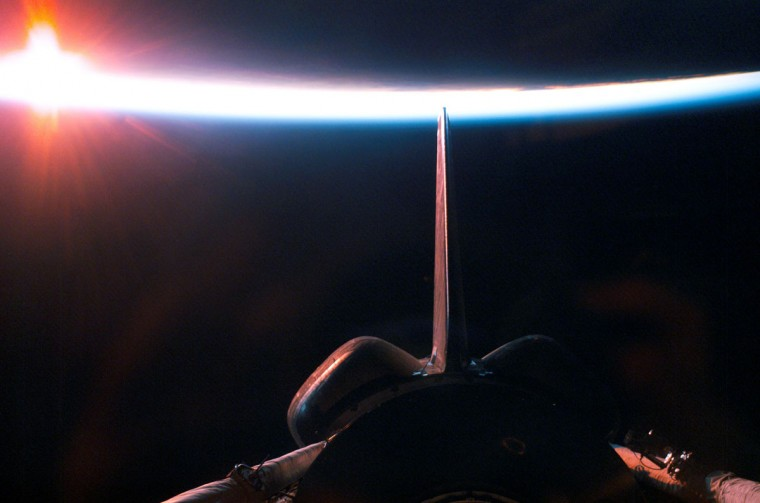 August 6, 2005: The sun illuminates the Earth's atmosphere during a sunrise, seen from the Space Shuttle Discovery after departure from the International Space Station. A portion of the shuttle's aft cargo bay, its vertical stabilizer and orbital maneuvering system (OMS) pods are seen in the foreground. (AP Photo/NASA)