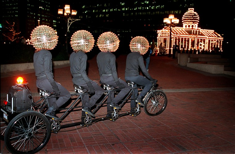 "In January 1998, ""Bubbleheads,"" a four person bicycle performance art piece created by New York artist Eric Staller for a Maryland College of Art show, pedals along the Inner Harbor promenade. (Amy Davis/Baltimore Sun)"