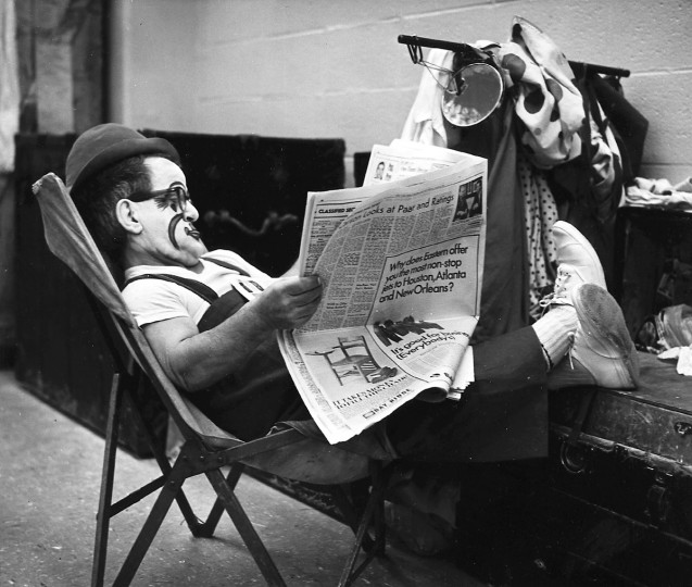 In 1966, a Ringling Brothers & Barnum Bailey circus clown kicks back and reads the paper until time to don his costume. (Richard Stacks/Baltimore Sun)
