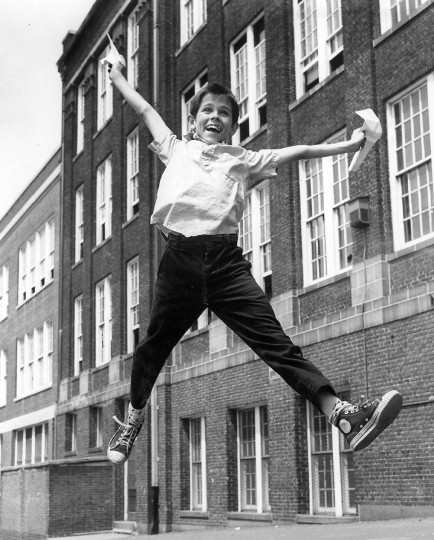 In June 1963, Raymond McGrew leaps with joy outside Public School No. 47 at Fleet Street and Linwood avenue as he gets his report card, showing that he passed. (Ellis Malashuk/Baltimore Sun)