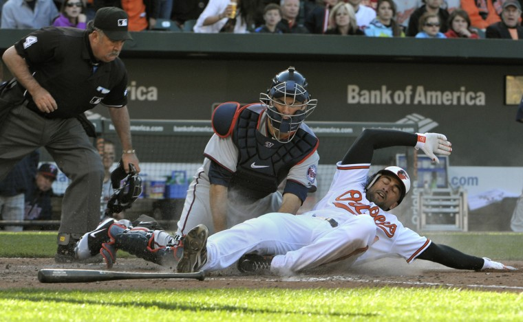 Orioles Nick Markakis is tagged out at the plate by Twins catcher Joe Mauer, after he tried to score on a Matt Wieters foul ball in the 6th inning. Umpire TimTschida is making the call. (Gene Sweeney, Jr./Baltimore Sun)