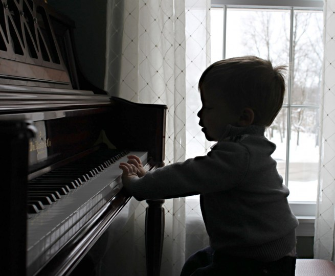 "Making Music: ""Starting Early with Making Music"" by Jean Wimmer -- Jean actually won twice with this image of her two-year-old grandson playing the piano. ""Generally, I'm not a big fan of silhouette photos. They tend to be overdone and I feel there are better ways to approach a subject that elicit more emotion. However, in this case, I feel the photographer was successful in using the backlight to isolate the subject and capture a very touching moment. There's seems to be a universal attraction between children and pianos."""