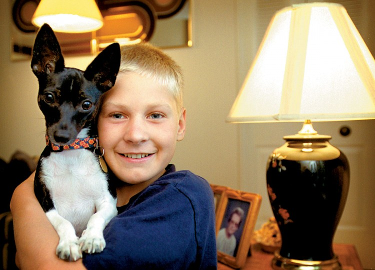 "July 25, 2001: Belarus native Vadzim Ihnatsyeu poses with Suzee, a toy fox terrier, owned by the American family Vadzim has been staying with for the past six weeks. Ten kids from Chernobyl area of the former Soviet Union traveled to the U.S. for six weeks to spend time away from the ""hot zone."" Vadzim was taken in by the Sopher family of Parkton, Maryland. (Patuxent Publishing)"