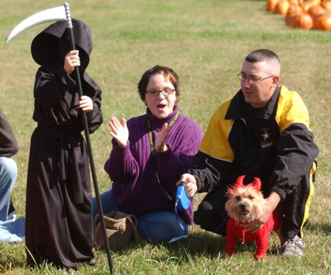 Heather Salada, center, of Ft. Meade, claps after her son Hunter, 6, left, and his dog Duncan were awarded first place in the scariest costume category during the Halloween Pet Parade and Costume Contest Saturday, October 23, 2004 at Ft. Meade. (Steve Ruark/Patuxent Publishing)