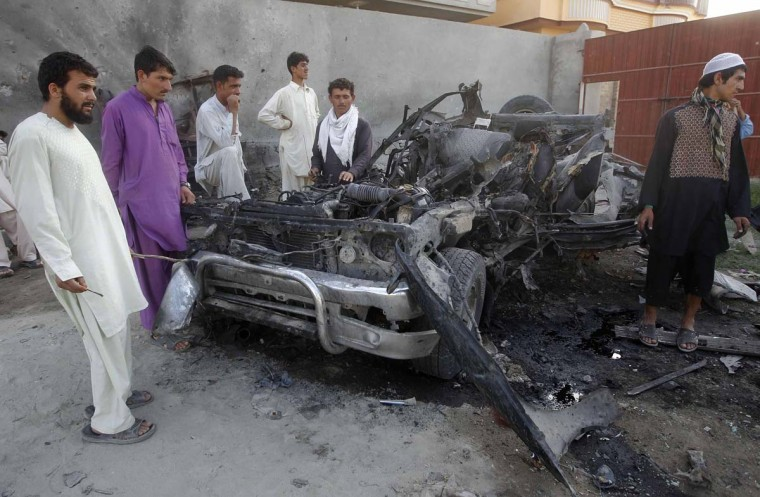 April 15: Afghan men stand around the wreckage of a car used by a suicide attacker in Jalalabad province. (Parwiz/Reuters)