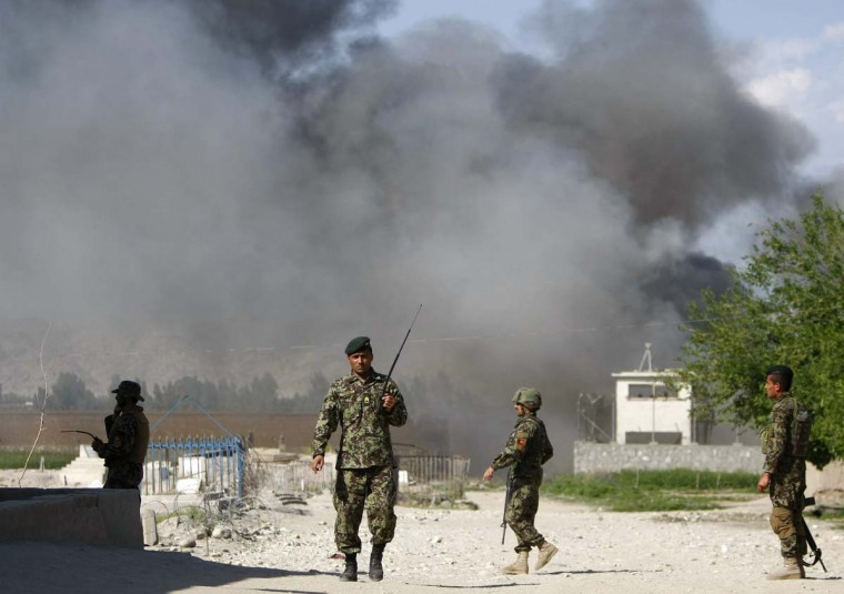 April 15: Soldiers from the Afghan National Army keep watch near the Provincial Reconstruction Team as smoke rises from the site of an attack in Jalalabad province. (Parwiz/Reuters)