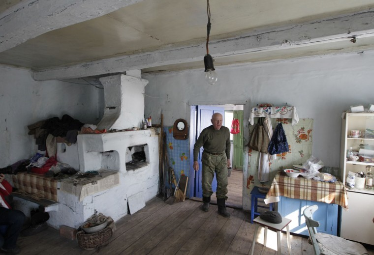 April 23, 2012: Villager Ivan Shamianok, 87, walks in his house at the abandoned village of Tulgovichi, near the exclusion zone around the Chernobyl nuclear reactor, some 370 km (230 miles) southeast of Minsk. Shamianok never left his village in spite of the Chernobyl blast, and he is now one of six last villagers that still live in Tulgovichi. (Vasily Fedosenko/Reuters)