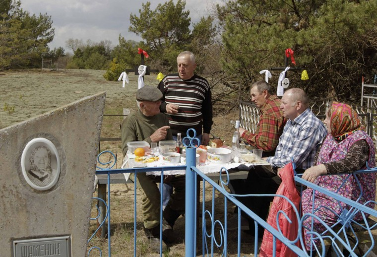 April 23, 2012: Villager Ivan Shamianok talks with former neighbours on the eve of Radunitsa at a cemetery in the abandoned village of Tulgovichi. Every year, residents who left their villages after the Chernobyl blast gather at the cemeteries for a day to visit their relatives' graves and to meet with former friends and neighbours. (Vasily Fedosenko/Reuters)