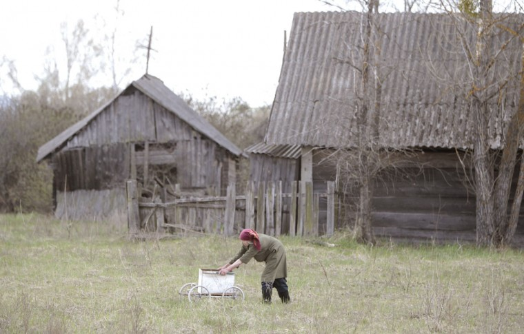 April 23, 2012: A Belarussian villager pushes a trolley containing products purchased from a mobile shop on the eve of Radunitsa, or the Day of Rejoicing, in the abandoned village of Tulgovichi, near the exclusion zone around the Chernobyl nuclear reactor. (Vasily Fedosenko/Reuters)