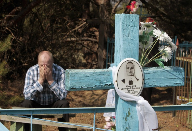 April 23, 2012: A Belarussian man sits at his relative's grave on the eve of Radunitsa in the abandoned village of Tulgovichi, near the exclusion zone around the Chernobyl nuclear reactor, some 370 km (230 miles) southeast of Minsk. (Vasily Fedosenko/Reuters)