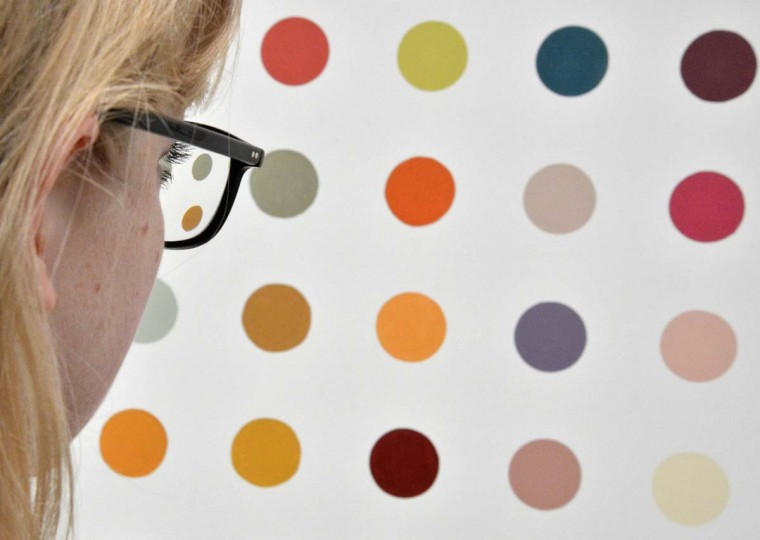 A visitor views a spot painting by British artist Damien Hirst. Hirst's retrospective show runs from April 4 to September 9. (Toby Melville/Reuters)