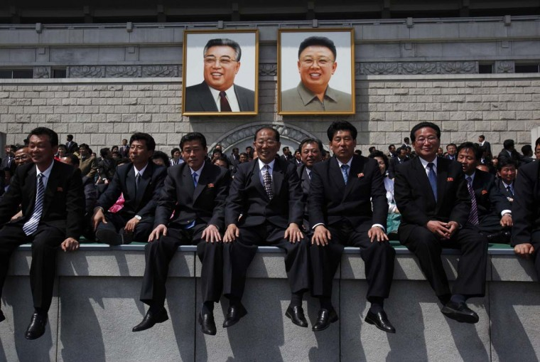 April 15: North Koreans sit in front of the podium with portraits of North Korea founder Kim Il-sung (left) and the late leader Kim Jong-il after a military parade. (Bobby Yip/Reuters)