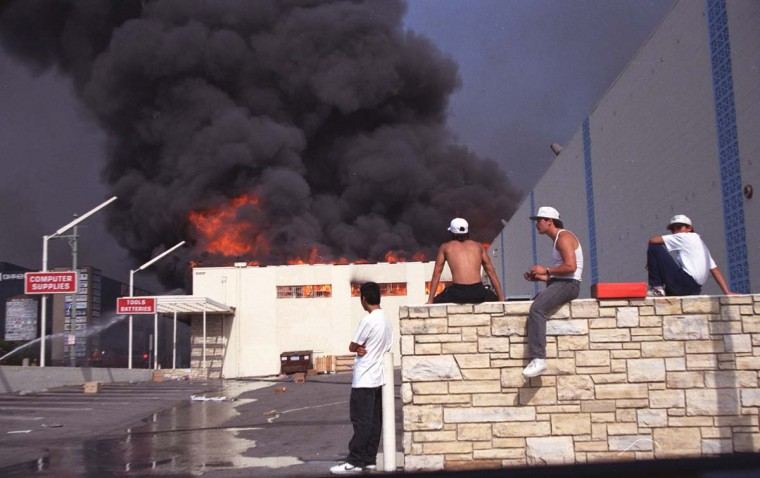 May 1, 1992: Onlookers watch as an electronics shop on Olympic Boulevard burns during the third day of the Los Angeles Riots in Koreatown. (Hyungwon Kang/Los Angeles Times/Files/Reuters)