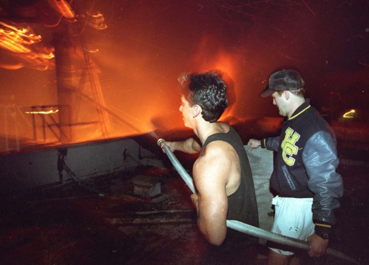 May 1, 1992: Residents fight fire with a water hose from an apartment building during the third night of the Los Angeles Riots in Koreatown. (Hyungwon Kang/Los Angeles Times/Files/Reuters)