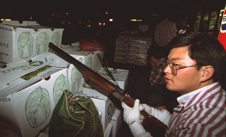 April 30, 1992: Armed volunteers take position behind cabbage boxes as they guard a California market from approaching looters during the second day of the Los Angeles Riots in Koreatown. (Hyungwon Kang/Los Angeles Times/Files/Reuters)