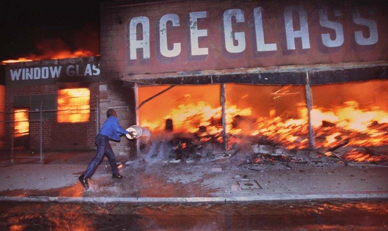 April 29, 1992: Cornelius Pettus, owner of Payless market, throws a bucket of water on the flames at neighboring business Ace Glass during the first night of the Los Angeles Riots in Los Angeles. (Hyungwon Kang/Los Angeles Times/Files/Reuters)