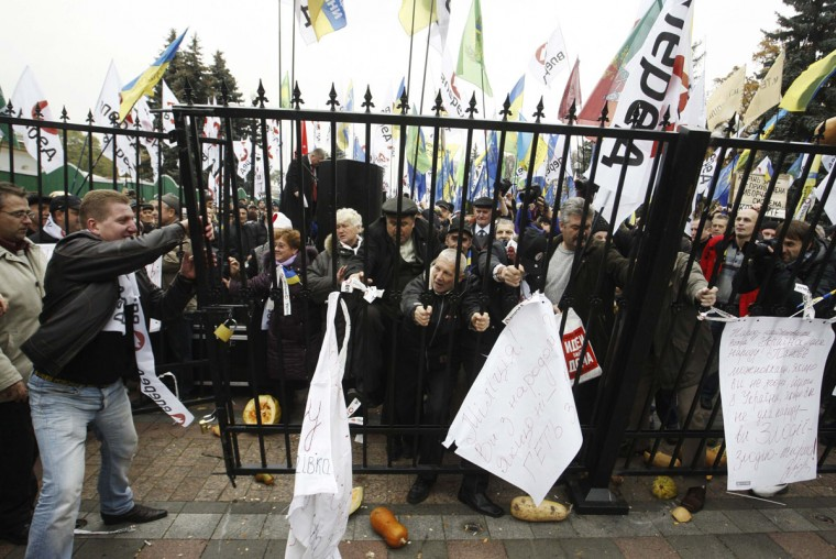 "November 3, 2011: Demonstrators demolish a fence during a protest rally in front of the Ukrainian parliament headquarters in Kiev. Participants, consisting of ""liquidators"" or emergency workers who fought the blaze at the Chernobyl nuclear reactor, veterans of the 1979-89 Soviet Afghan war and supporters of opposition organizations, tried to storm into the parliament building protesting against government policies, and in particular, plans to cut their payouts and subsidies, according to local media. (Vladimir Sindeyev/Reuters)"