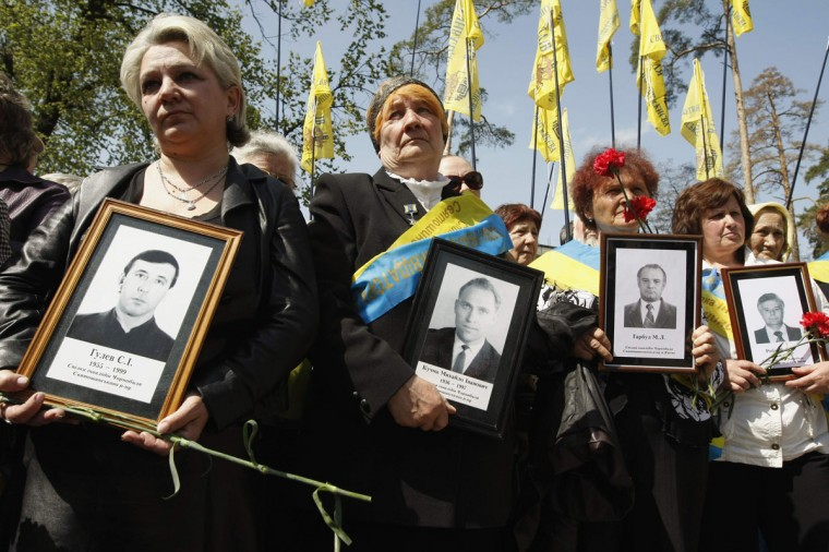 April 26, 2012: People hold portraits of victims of the Chernobyl nuclear accident, during a ceremony in Kiev. (Anatolii Stepanov/Reuters)