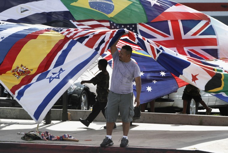 April 29, 2012: Jose Elias holds up a banner featuring various national flags during a rally marking the 20th anniversary of the LA riots at the intersection of Florence and Normandie. (Jonathan Alcorn/Reuters)