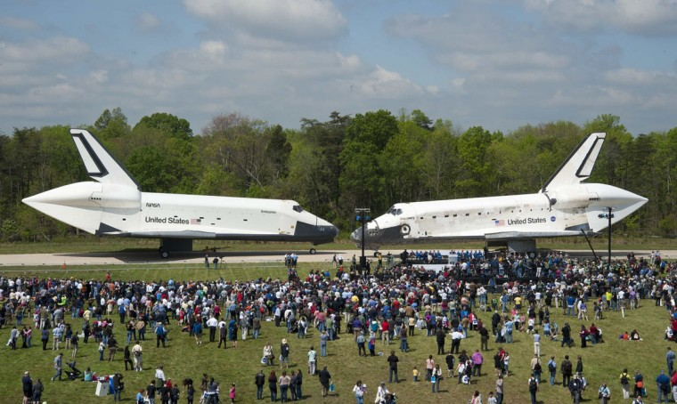 April 19, 2012: Space Shuttles Enterprise, left, and Discovery meet nose-to-nose at the beginning of a transfer ceremony at the Smithsonian's Steven F. Udvar-Hazy Center, in Chantilly, Virginia. Space shuttle Discovery, the first orbiter retired from NASA's shuttle fleet, traveled total 148,221,675 miles and will take the place of Enterprise at the center to commemorate past achievements in space and to educate and inspire future generations of explorers at the center. (NASA/Smithsonian Institution/Carolyn Russo/Reuters)