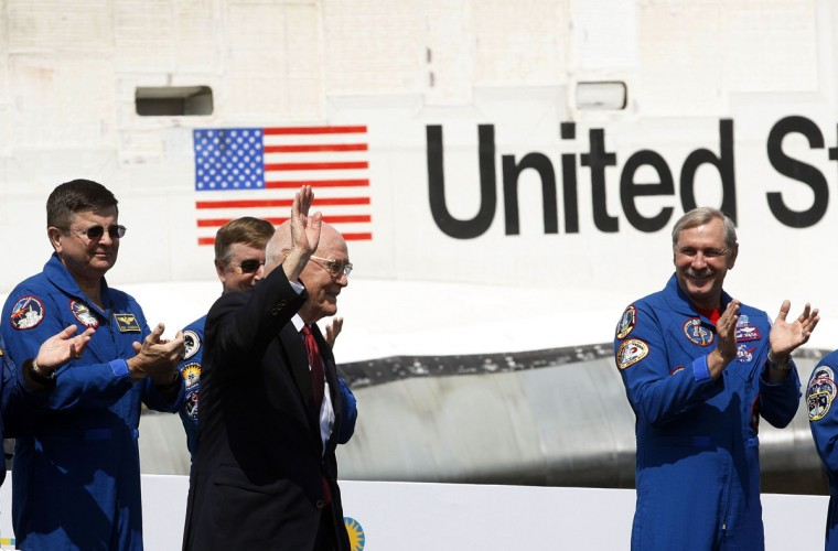 April 19, 2012: Former U.S. Senator and astronaut John Glenn (C) waves to the crowd at the National Air and Space Museum's Udvar-Hazy Center for the arrival of space shuttle Discovery (back) while former shuttle commanders applaud in Virginia. (Gary Cameron/Reuters)
