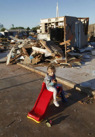 Edie Paroish, 3, of Woodward, Oklahoma, plays on a slide in front of a destroyed home following a tornado that struck the town April 15, 2012. Rescue and clean-up efforts were underway across the Midwest on Sunday after dozens of tornadoes tore through the region, killing at least five people in Oklahoma, leaving thousands without power in Kansas and damaging up to 90 percent of the homes and buildings in one small Iowa town. (Jeff Tuttle/Reuters)