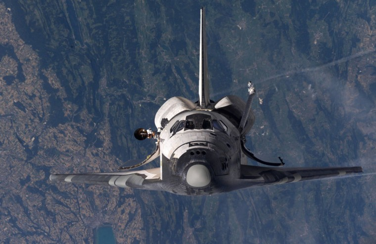 July 28, 2005: Space Shuttle Discovery is shown approaching the International Space Station prior to docking. (NASA/Getty Images)