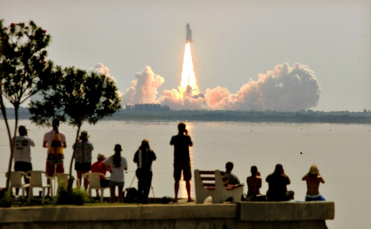 July 26, 2005: Space Shuttle Discovery lifts off from launch pad 39B at Kennedy Space Center as onlookers watch in Titusville, Florida. Discovery is the first shuttle launched since the Columbia disaster over two years ago. (Mario Tama/Getty Images)