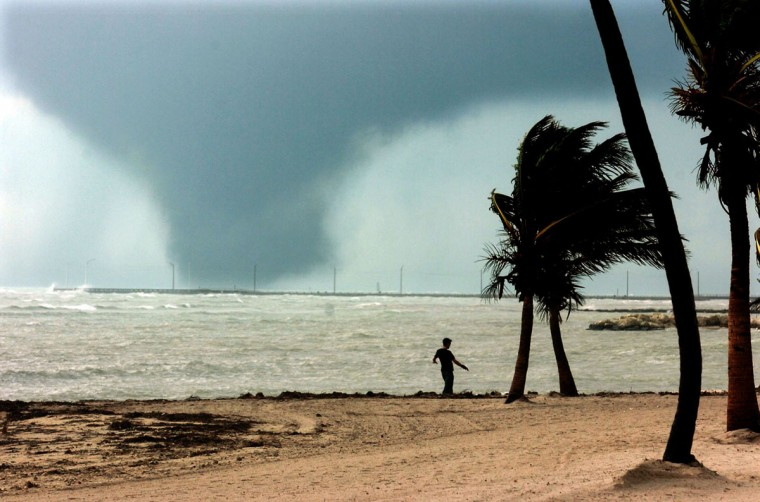 A large waterspout (tornado) from the first feeder bands of Hurricane Wilma approach Key West, Florida, as a man walks on the beach Sunday, October 23, 2005.(Tim Chapman/Miami Herald)