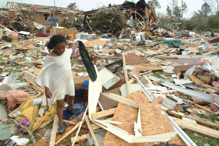 Shantsy Hardwick, 9, retrieves clothing from the rubble of the mobile home that she and her mother were in when a tornado struck and demolished it early Thursday, March 20, 2003 in Camilla, Georgia. They suffered only minor injuries, but at least six people were killed by the storm. (Todd Stone/(AP Photo)