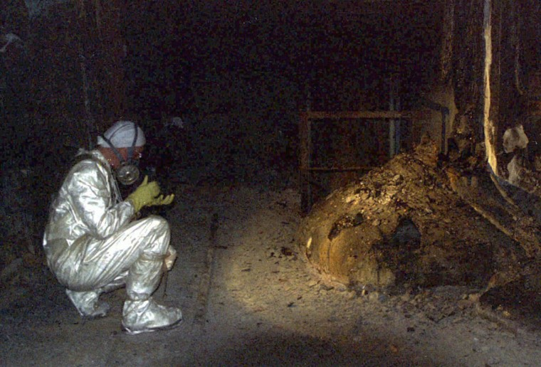 "April 17, 1996: A worker at the Chernobyl nuclear power plant takes a reading of radioactivity inside the ""tomb"" encasing the ruined fourth reactor. Readings here in 1996 were 800 roentgens per minute, one-tenth of what they were by the ""elephant's foot"" - the tangled mass of concrete and steel at the right of the nuclear fuel which melted in the accident. (Stringer/Reuters)"