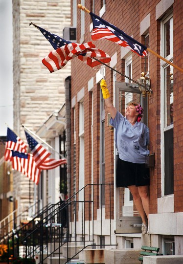 On July 3, 1997, while Evelyn Anderson was busy scrubbing her marble steps in the 1200 block of Hull Street in Locust Point, a gust of wind tangled her new flags set out for tomorrow's celebration. Using a bit of ingenuity, she unfurled the flag using a clothes hanger for the extra reach. (Larry C. Price/Baltimore Sun)
