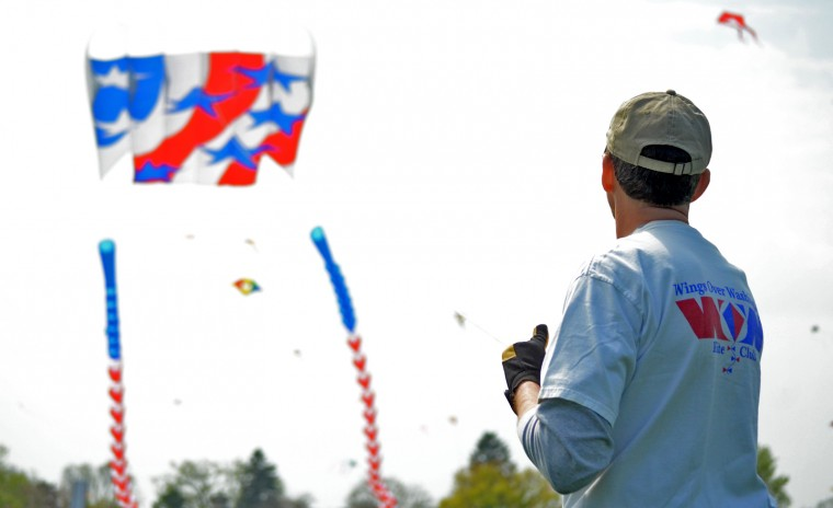 A Kite Festival participant hoists a large patriotic kite into the air in an open field. Due to the kite's size, it was a bit of a struggle to get it flying. (Jon Sham/Patuxent Homestead)