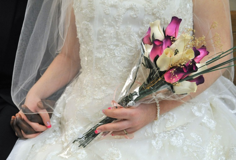 Feb. 15: Bride and groom, Holly Atwood, 18, and Steven Joseph, 21, of Conowingo hold hands as their wait for their turn to exchange wedding vows in the wedding chapel at the Baltimore County Courthouse on Valentine's Day. The bride had a bouquet made of wooden roses, so that she could keep them forever. (Amy Davis/Baltimore Sun)