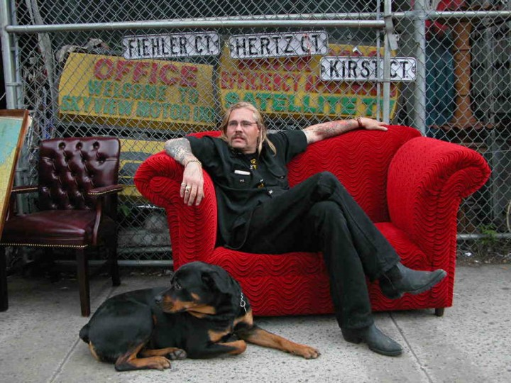 "Red: ""Billy Leroy"" by Sandra Nicht -- Sandra photographed antique and prop store owner Billy Leroy and his dog sitting on a couch on the sidewalk in New York City. ""There were a lot of great photos this week. I chose this one because the red couch is as much a character in this photo as Billy and his dog. Sandra did a nice job composing the photo so the main subjects stand out against what looks to be a cluttered background."""