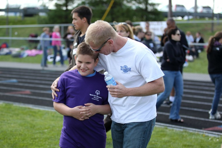 Dennis Null, right, hugs his stepson Westminster Elementary's Robert Whitcomb, left, 9, after Robert placed first place in his heat during the Special Olympics Carroll County Spring Games. (Jen Rynda/Patuxent Homestead)